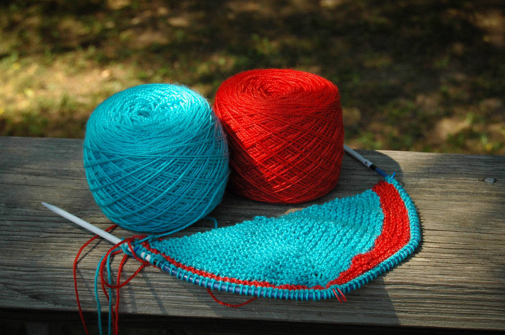 knitting blue and red yarn with needles